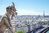 stock photo of demons  - Gargoyle Stryge and demon at Notre Dame of Paris overlooking the skyline at a summer day  - JPG
