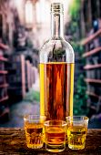image of whiskey  - Bottle and three glass shots with yellow liqour resembling whiskey - JPG
