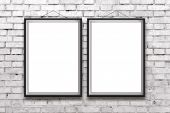 pic of wall painting  - Two blank vertical painting or posters in black frame hanging on white brick wall - JPG