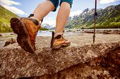 stock photo of follow-up  - Hiking boot close up on mountain rocks - JPG