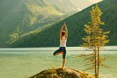 picture of  practices  - Young woman is practicing yoga at mountain lake - JPG