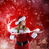 picture of presenter  - Sexy santa girl presenting with hand against red snow flake pattern design - JPG