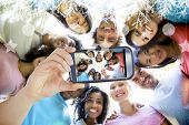 foto of huddle  - Hand holding smartphone showing friends forming huddle - JPG