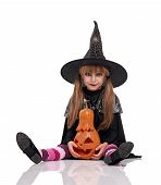 stock photo of warlock  - Little girl in black hat with pumpkin sitting on floor - JPG