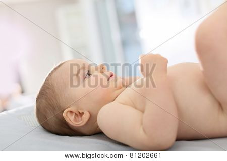 Baby boy laying on changing table in bedroom