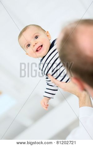 Daddy holding baby boy up in the air