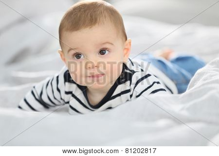 Cheerful baby boy laying over bed
