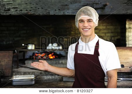 Man Working At A Restaurant Showing Wood-fired Oven