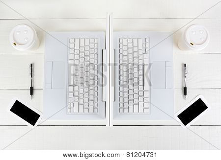 High angle shot of two laptop work stations back-to-back with almost identical layouts. Horizontal format on a white wood table.