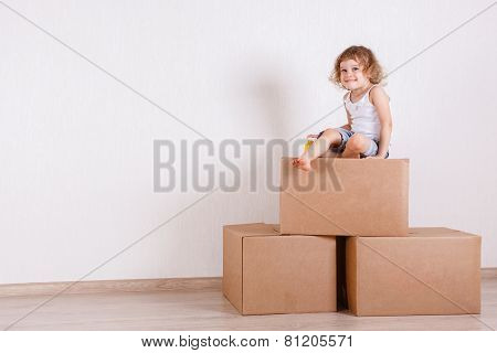 Child Sits In A Room On The Boxes.