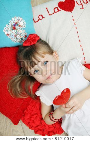 Girl On The Pillows Holding A Lollipop