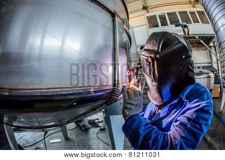 Man welding with reflection of sparks on visor. Hard job.