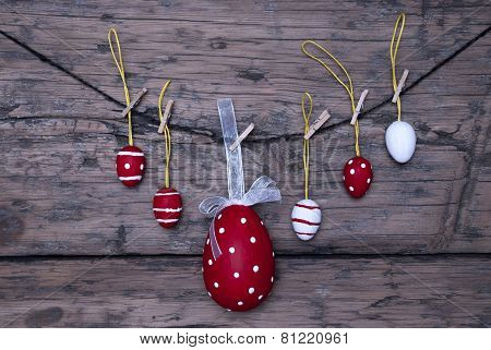 Many Red And White Easter Eggs And One Big Egg Hanging On Line