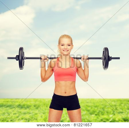 fitness, sport and dieting concept - smiling sporty woman exercising with barbell