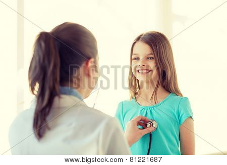 healthcare, child and medical concept - female doctor with stethoscope listening to child chest in hospital
