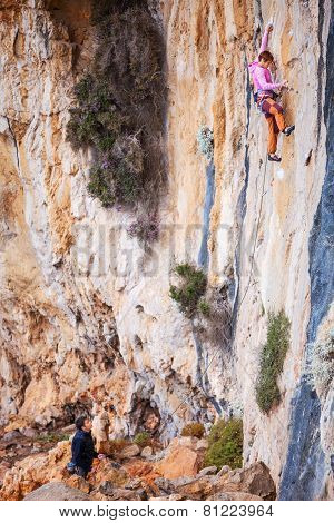Young woman lead climbing on natural cliff