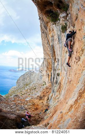 Young man lead climbing on cliff near sea