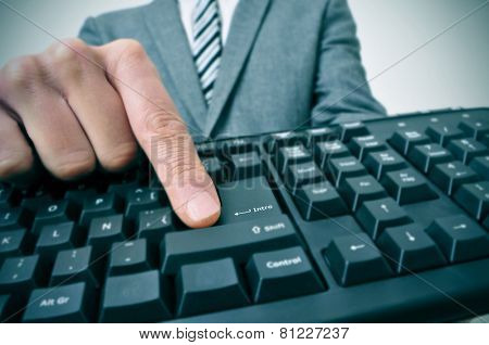 closeup of a businessman pressing the inter key of a computer keyboard