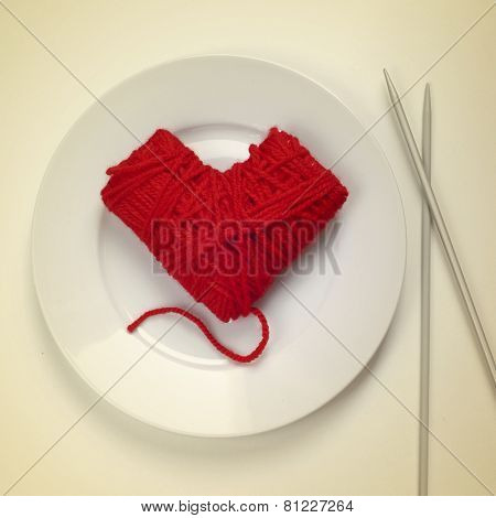 a heart-shaped ball of yarn in a plate and knitting needles at the side, as the flatware, with a retro effect