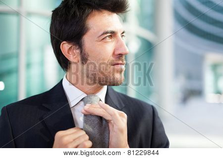 Confident businessman adjusting his necktie