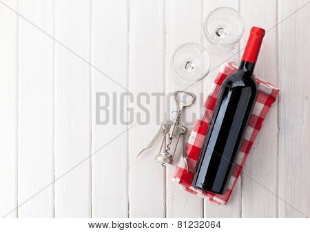 Red wine bottle, glasses and corkscrew on white wooden table background with copy space