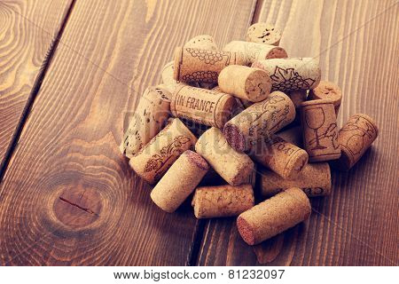 Wine corks heap over rustic wooden table background. Retro toned