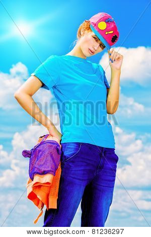 Young stylish girl posing over blue sky. Youth fashion. Hip-hop style.