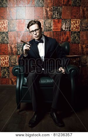Handsome young man in elegant suit smoking a cigar. He is sitting on a leather chair in a luxurious interior.