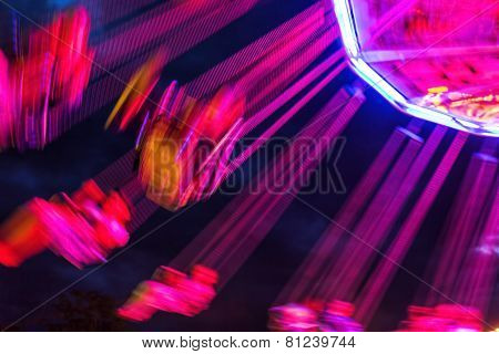 Traditional chain carousel with motion blur at night