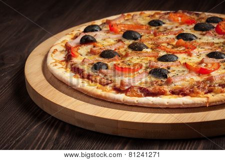 Ham pizza with capsicum and olives on wooden board on table close up