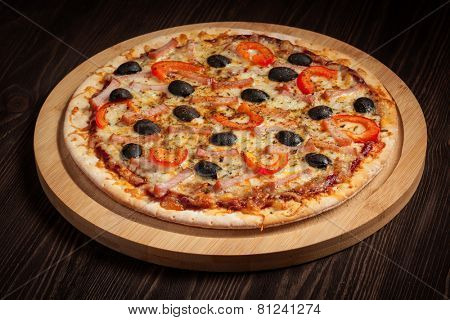 Ham pizza with capsicum and olives on wooden board on table