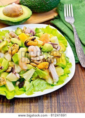 Salad seafood and avocado on dark board