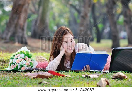 Women Sitting On Wooden Mat And Reading Book.