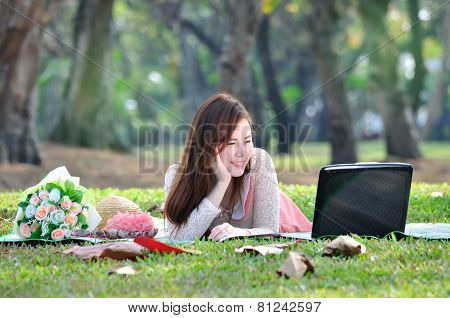 Women Sitting On Wooden Mat And Watching Notebook Computer.