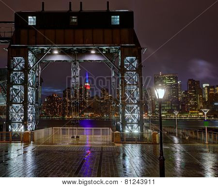 Manhattan New York skyline rainy night from East River floodgates structure USA