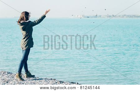 Young Woman Throwing Stones In The Sea