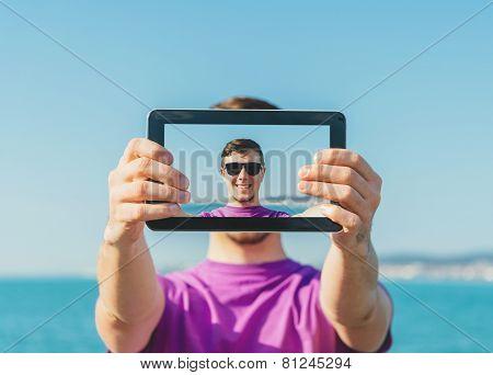 Man Doing A Self-portrait With Him Digital Tablet On Beach