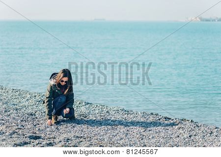 Young Woman Collects Stones On Coastline