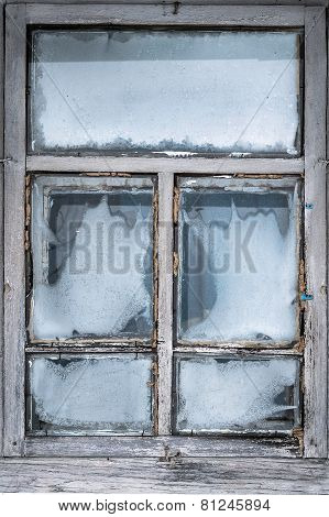 Misted snow-covered window country house
