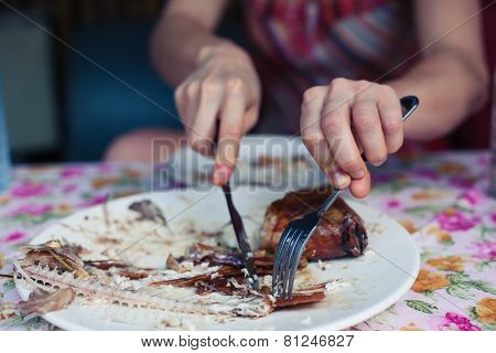 Woman Eating Fish In Restaurant