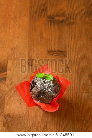 overhead view of chocolate muffin in the red paper basket, decorated with piece of mint