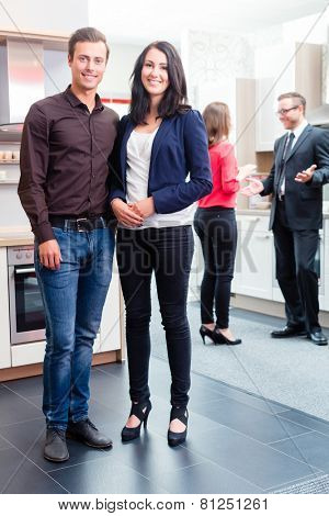 Couple buying in kitchen in store showroom