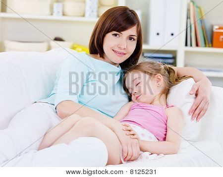 Mother With Sleeping Daughter At Home