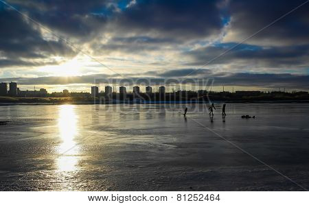 Ice Skating Children Play On The Bay At Sunset