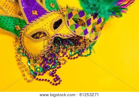 A venetian, mardi gras mask or disguise on a yellow background