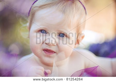 Portrait of a little girl among the flowers of lavender.