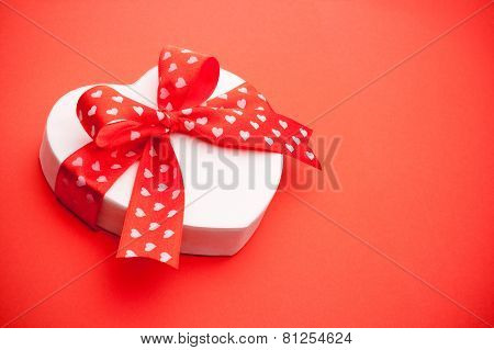 Gift In The Form Of Heart Tied With Red Ribbon With A Bow On Red Background