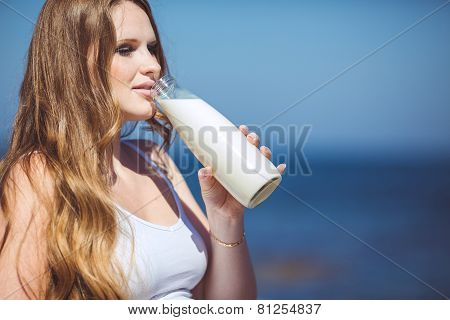 Pregnant woman on the beach drinking milk from a bottle.