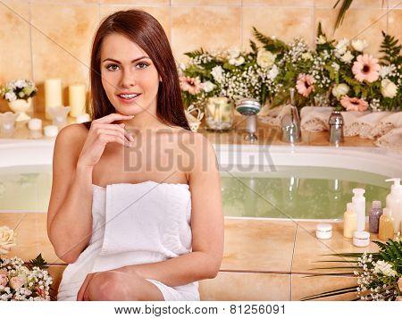 Woman relaxing at water spa. Girl sitting near a bath tub