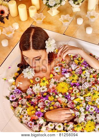 Woman relaxing at water spa. Girl takes a bath with flowers
